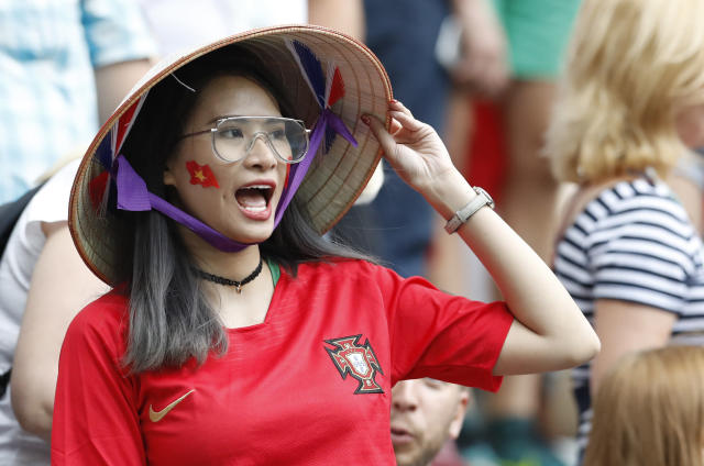 FILE - In this Wednesday, June 20, 2018 file photo, a Portugal supporter cheers from the stands during the group B match between Portugal and Morocco at the 2018 soccer World Cup at the Luzhniki Stadium in Moscow, Russia, Wednesday, June 20, 2018. Chinese sponsors are more visible than ever and tens of thousands of Chinese fans have descended on Moscow, using their growing economic clout to secure top-dollar seats and dreaming of the day, perhaps not that far off, when China will host football's showcase. (AP Photo/Antonio Calanni, File)