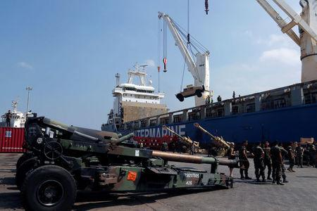 Workers unload a Humvee, as Lebanese Army soldiers stand near Howitzers, part of a military donation from the U.S. government to the Lebanese army, during a ceremony at Beirut's port