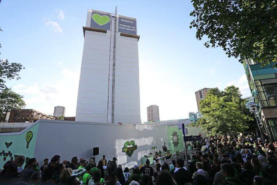 Family and friends of the 72 people who lost their lives in the Grenfell Tower block fire gather at the scene in June. (PA)