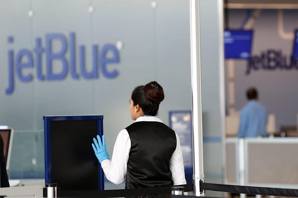 A TSA employee raises her hand to stop passengers in front of a JetBlue sign