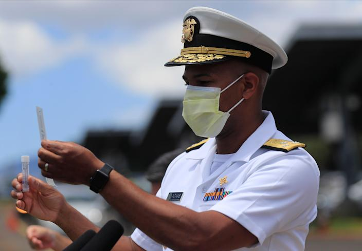 U.S. Surgeon General Jerome Adams demonstrates the self-administered COVID-19 swab test on Wednesday, Aug. 26, 2020 at Leeward Community College in Pearl City, Hawaii.