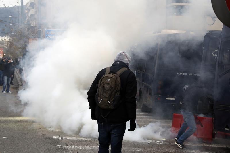Riot police throw a tear gas canister at teachers and other protesters, during clashes near the Prime Minister's office in Athens, Friday, Jan. 11, 2019. About 1,500 people took part in the protest. Teachers' unions oppose the government's selection process for the planned hiring of 15,000 new teachers over the next three years. (AP Photo/Thanassis Stavrakis)
