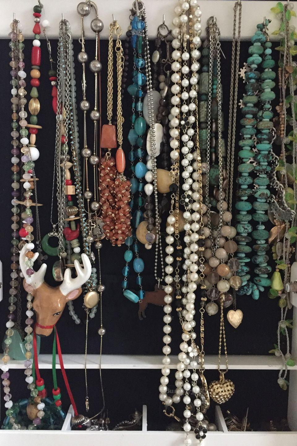 """<p>Hang a flat <a href=""""https://www.womansday.com/style/fashion/g2304/mothers-day-jewelry/"""" rel=""""nofollow noopener"""" target=""""_blank"""" data-ylk=""""slk:jewelry"""" class=""""link rapid-noclick-resp"""">jewelry</a> organizer with transparent pockets inside your closet door.</p><p><strong><a class=""""link rapid-noclick-resp"""" href=""""https://www.amazon.com/Homeneeds-Hanging-Jewelry-Organizer-Make-Up/dp/B071ZBLTYW?tag=syn-yahoo-20&ascsubtag=%5Bartid%7C10070.g.3310%5Bsrc%7Cyahoo-us"""" rel=""""nofollow noopener"""" target=""""_blank"""" data-ylk=""""slk:SHOP JEWELRY ORGANIZERS"""">SHOP JEWELRY ORGANIZERS</a></strong></p>"""