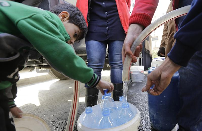 Damascus residents fill plastic containers with water provided by the Syrian Arab Red Crescent in the capital on January 10, 2017 (AFP Photo/LOUAI BESHARA)