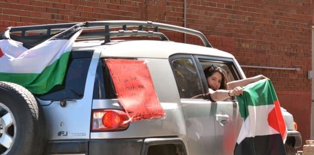 Nada Musa holds the Palestinian flag out the window of a car during the pro-Palestinian demonstration in Halifax on Saturday.