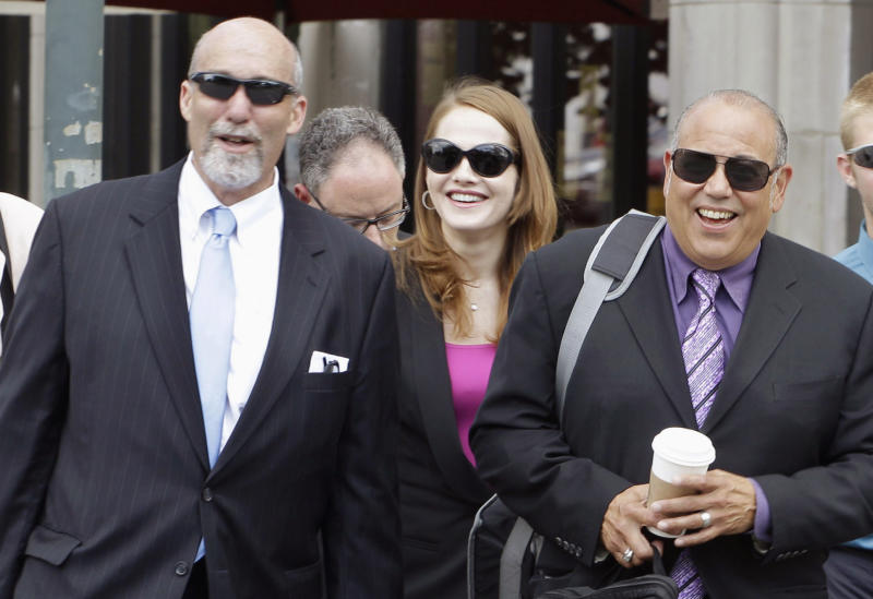 "FILE - In this July 31, 2012 file photo, defense attorneys from left, Joel Brodsky, Lisa Lopez, and Joe Lopez return to the Will County Courthouse in Joliet, Ill., from a break after giving opening statements in the murder case of former Bolingbrook, Ill., police officer Drew Peterson, who is charged in the 2004 death of his third wife, Kathleen Savio. For more than month, the jurors at Peterson's trial have caused a stir by been coming into court wearing matching clothes _ all yellow one day; other days black, blue and green. They've even filed in wearing alternating red, white and blue. And the coordinated attire hasn't been just about color. Once, it was all business suits. Then there was the day they all wore jerseys from sports teams _ mostly Bears and White Sox, though one was a Green Bay Packers shirt, and none for the Cubs. ""If they came in wearing T-shirts saying 'Drew's Guilty,' it'd be different,"" said Lisa Lopez. ""I think it means they are unified about coming to a decision."" (AP Photo/M. Spencer Green, File)"