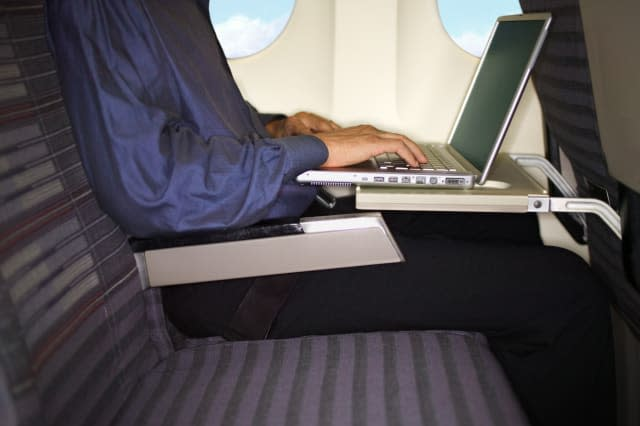 Person working on laptop computer in seat on plane.