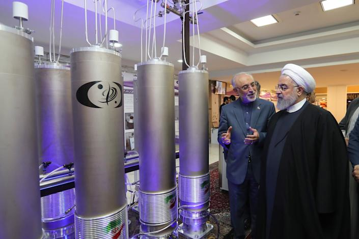 Iranian President Hassan Rouhani (R) and the head of Iran nuclear technology organization Ali Akbar Salehi inspect nuclear technology in Tehran in April 2019: EPA