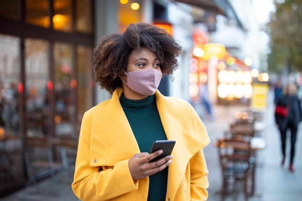 Woman in the city wearing face mask and holding cell phone