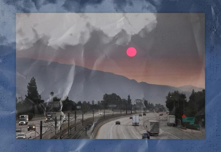 Smoke from wildfires darkens the sky over the mountains and freeway.