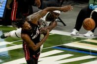 Miami Heat's Trevor Ariza and Milwaukee Bucks' Jrue Holiday go after a loose ball during the first half of an NBA basketball game Saturday, May 15, 2021, in Milwaukee. (AP Photo/Morry Gash)