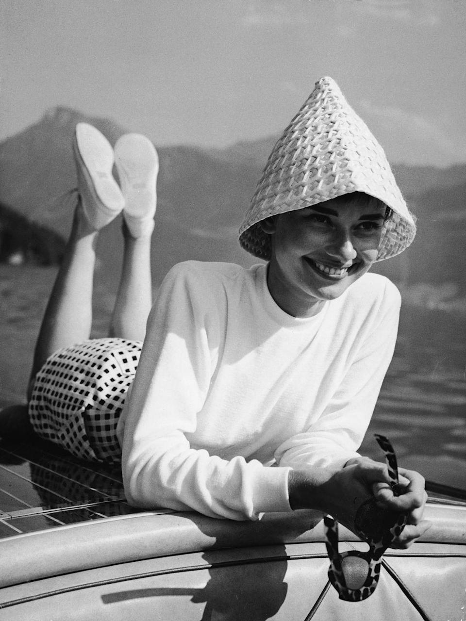 <p>Audrey Hepburn lays across the bow of a motorboat during a day on the water. The stylish actress wears a gingham print skirt, white mock turtleneck, and woven sun hat. </p>