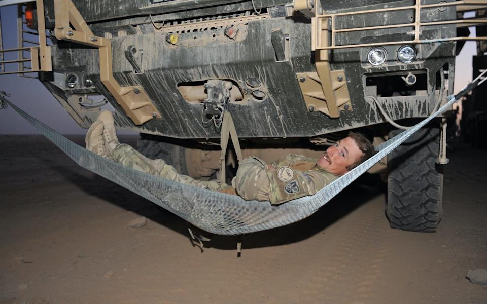 A soldier sets up his bed on an overnight Combat Logistics Patrol, somewhere in the Helmand desert. - Rupert Frere RLC/Crown Copyright