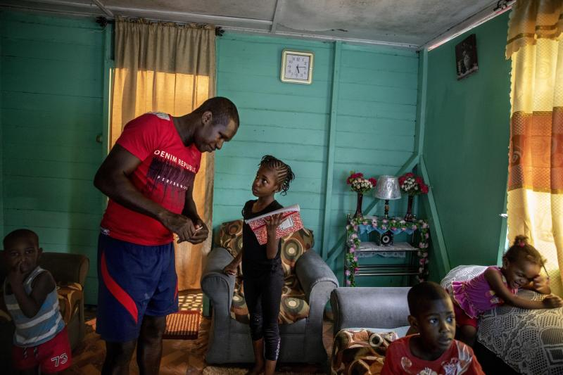 "Fisherman Damian Brown helps his daughter Mishaunda, 9, with her homework as his sons Damian Jr., 3, from left, Dre, 4, and daughter Paris, 1, right, watch television in their home in Stewart Town, Jamaica, Thursday, Feb. 14, 2019. Brown has been caught twice fishing inside a no-take zone and now relies more on night spearfishing, which is illegal, to make up for the wages impacted by the sanctuary's restrictions. ""Was nice before the sanctuary come in. Was good,"" said Brown. ""Now I make no money off the sea again like one time."" (AP Photo/David Goldman)"