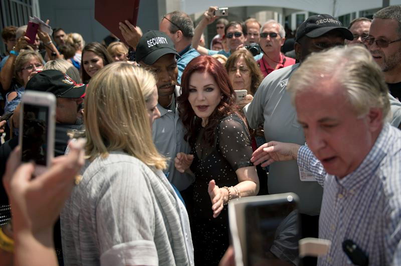 Priscilla Presley, center, former wife of Elvis Presley, is escorted by security after greeting fans at Elvis Presley's Memphis home, near Graceland on Tuesday, Aug. 15, 2017, in Memphis, Tenn. Fans from around the world are at Graceland for the 40th anniversary of the rock n' roll icon's death. (AP Photo/Brandon Dill)