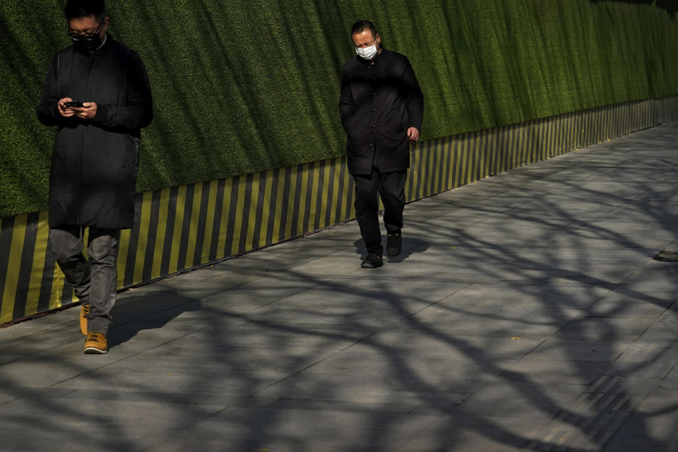 People wearing face masks to help curb the spread of the coronavirus walk by tree shadows at the Central Business District in Beijing, Tuesday, Nov. 24, 2020. China has reported new coronavirus cases in the cities of Shanghai and Tianjin as it seeks to prevent small outbreaks from becoming larger ones. (AP Photo/Andy Wong)