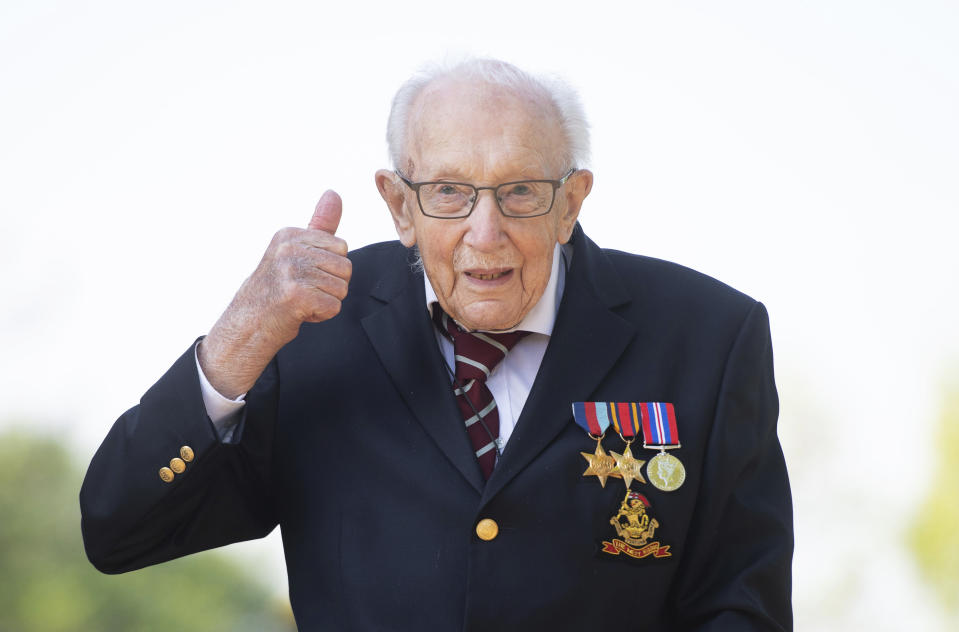 FILE - In this April 16, 2020, file photo, Captain Tom Moore gestures at his home in Marston Moretaine, Bedfordshire, England. The British army veteran who shuffled the length of his garden 100 times to raise funds for the National Health Service is to be honored with a knighthood. Moore received a special nomination for the honor from Prime Minister Boris Johnson, announced on Tuesday, May 19, just weeks after he raised 33 million pounds ($40 million) for completing a challenge to mark his 100th birthday. (Joe Giddens/PA via AP, File)