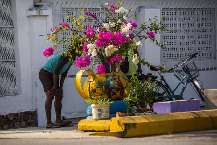 People stand behind a sidewalk flower pot watch as soldiers and police remove improvised barricades installed by anti-coup protesters and residents to secure a neighborhood from security forces in Yangon, Myanmar Thursday, March 18, 2021. (AP Photo)