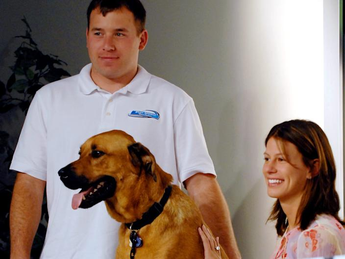 NASCAR driver Ryan Newman, left, is pictured with his wife wife Krissie, right, and dog Mopar during a news conference where the Ryan Newman Foundation announced the nationwide release of a book it published entitled Pit Road Pets at the Daytona International Speedway in Daytona Beach
