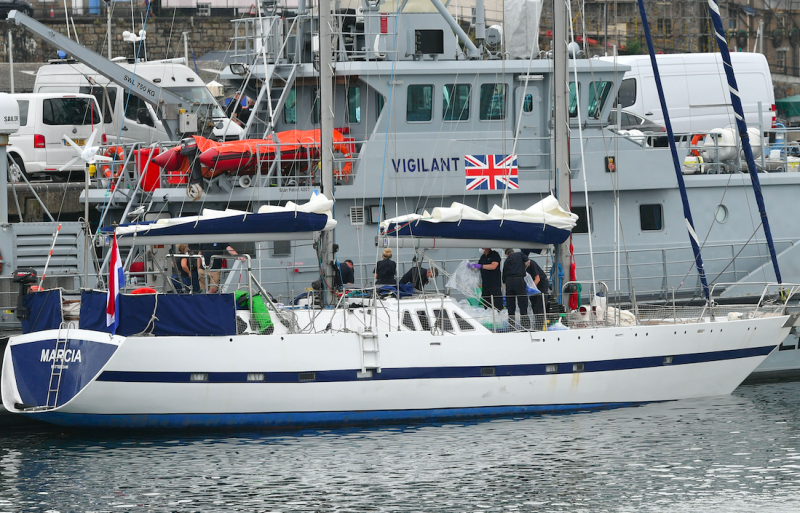 Drugs are unloaded from a boat by officers at Newlyn harbour, with the Border Force cutter HMC Vigilant behind (PA)