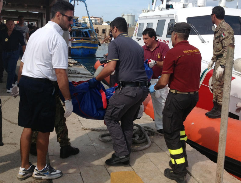Firefighters unload the body of a drowned migrant from a Coast Guard boat in the port of Lampedusa, Sicily, Thursday, Oct. 3, 2013. Tens of people died when a ship carrying African migrants toward Italy caught fire and sank off the Sicilian island of Lampedusa, spilling hundreds of passengers into the sea, officials said Thursday. Many migrants have been rescued, but the boat is believed to have been carrying as many as 500 people. It is one of the deadliest migrant shipwrecks in recent times and the second one this week off Italy: On Monday, 13 men drowned while trying to reach southern Sicily when their ship ran aground just a few meters (yards) from shore at Scicli. (AP Photo/Nino Randazzo, Health Care Service, HO)