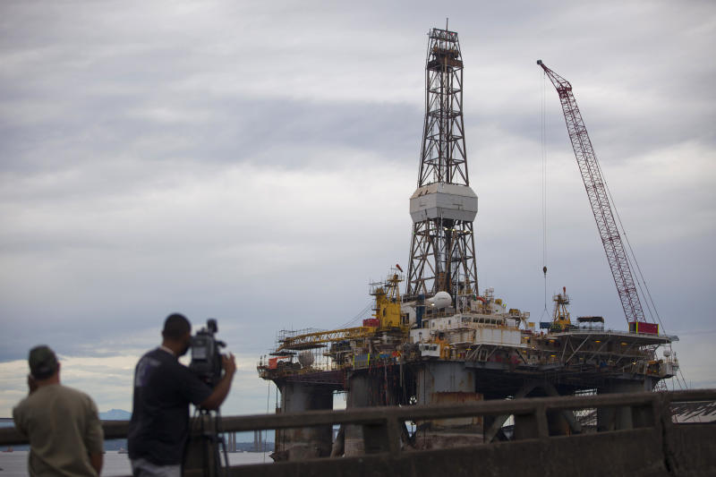 FILE - In this April  29, 2012 photo, a television news crew films from behind an exit guardrail the Transocean Ltd. offshore oil rig in Guanabara Bay in Rio de Janeiro, Brazil. Brazilian lawmakers are struggling over how to spread any wealth from the country's vast and recently discovered offshore oil reserves. The battle pits states close to the oil deposits against those further away. (AP Photo/Felipe Dana, File)