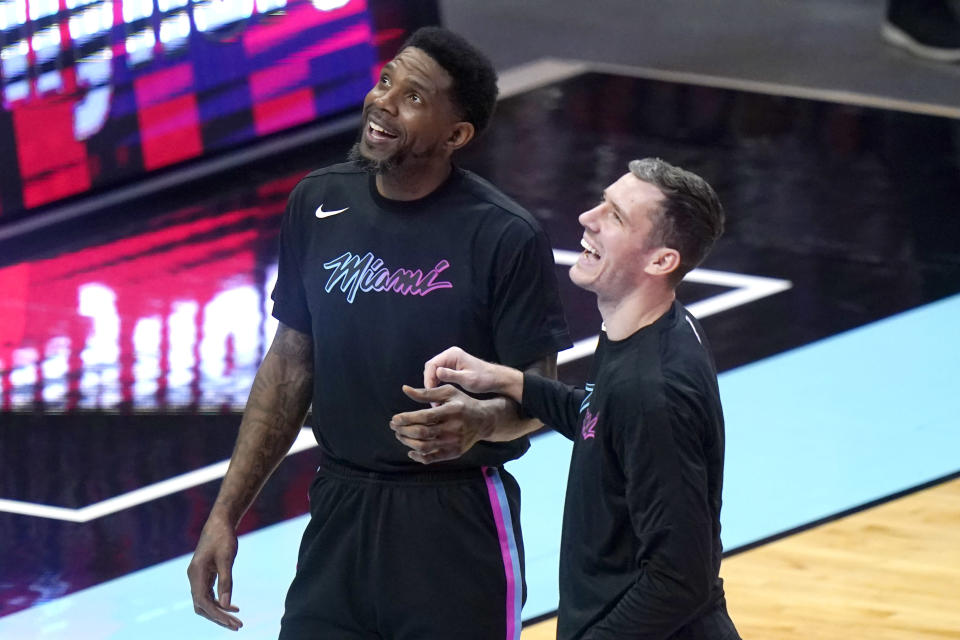 Miami Heat forward Udonis Haslem, left, talks with guard Goran Dragic before the team's NBA basketball game against the Philadelphia 76ers, Thursday, May 13, 2021, in Miami. (AP Photo/Lynne Sladky)