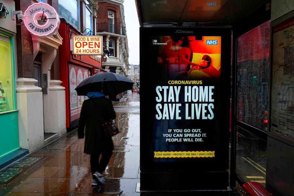 """A pedestrians walks past NHS signage promoting """"Stay Home, Save Lives"""" on a bus shelter in London (Photo: NIKLAS HALLE'N via Getty Images)"""