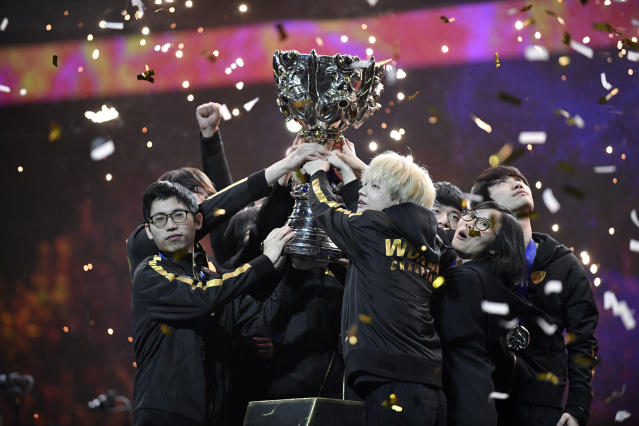 Team FunPlus Phoenix hold the trophy as they celebrate after winning the final of League of Legends tournament against Team G2 Esports, in Paris, Sunday, Nov. 10, 2019. The biggest e-sports event of the year saw a Chinese team, FunPlus Phoenix, crowned as world champions of the video game League of Legends. Thousands of fans packed a Paris arena for the event, which marked another step forward for the growing esports business. (AP Photo/Thibault Camus)