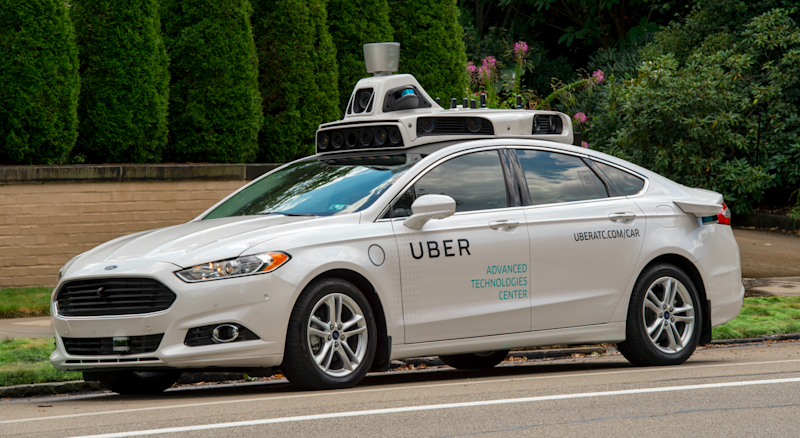 White car with Uber logo on side and self-driving equipment on the roof.