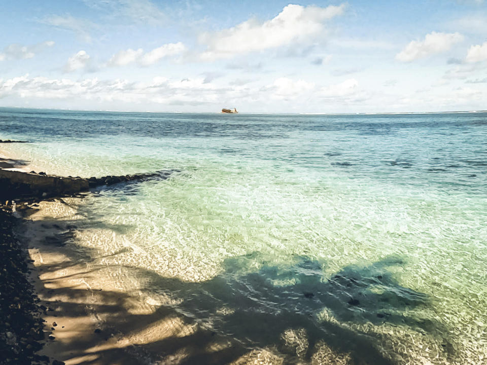 "In this photo provided by Grégoire Rouxel is a ship in the distance that ran aground in the ocean earlier this week, Friday, Aug. 7, 2020, in Mauritius. The Indian Ocean island of Mauritius has declared a ""state of environmental emergency"" after a Japanese-owned ship that ran aground offshore days ago began spilling tons of fuel. Prime Minister Pravind Jugnauth announced the development late Friday, Aug. 7, as satellite images showed a dark slick spreading near environmental areas the government called ""very sensitive."" (@gregrouxel via AP)"