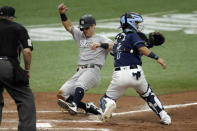 New York Yankees' Mike Tauchman scores ahead of the throw to Tampa Bay Rays catcher Michael Perez (7) on a sacrifice fly by Gio Urshela off Rays relief pitcher Oliver Drake during the seventh inning of the first game of a doubleheader baseball game Saturday, Aug. 8, 2020, in St. Petersburg, Fla. Makeing the call is home plate umpire Hunter Wendelstedt. (AP Photo/Chris O'Meara)