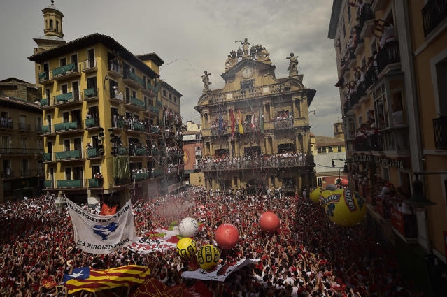 <p>People celebrate during the launch of the <em>chupinazo</em> rocket to celebrate the official opening of the 2017 San Fermín Fiesta. (Photo: Alvaro Barrientos/AP) </p>