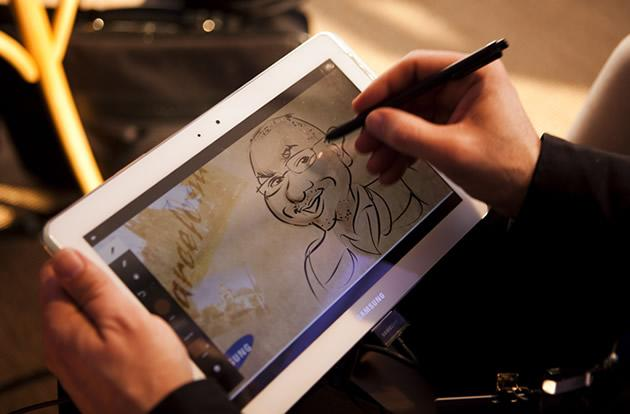 Artist Pedro Jose Espinosa draws a visitor on a Samsung Galaxy Note 10.1 tablet.