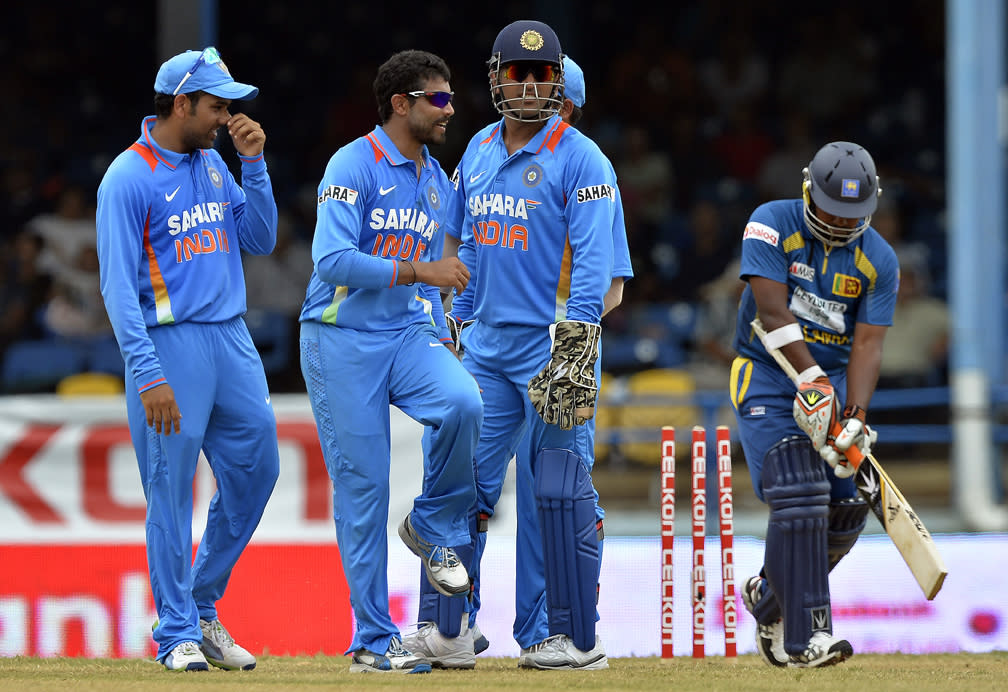 Indian cricketer Ravindra Jadeja (C) celebrates with teammates after dismissing Sri Lankan Rangana Herath during the final match of the Tri-Nation series between India and Sri Lanka at the Queen's Park Oval stadium in Port of Spain on July 11, 2013. India won the toss and elected to field first. AFP PHOTO/Jewel Samad