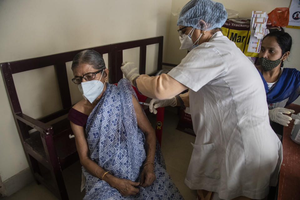 An elderly woman receives the AstraZeneca vaccine for COVID-19 at a government run in Gauhati, India, Saturday, May 8, 2021. Infections have swelled in India since February in a disastrous turn blamed on more contagious variants as well as government decisions to allow massive crowds to gather for religious festivals and political rallies. (AP Photo/Anupam Nath)