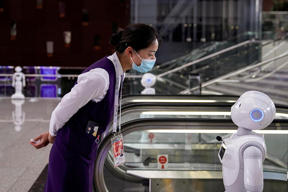 A staff member, wearing a face mask following the coronavirus disease (COVID-19) outbreak, looks at a robot at the venue for the World Artificial Intelligence Conference (WAIC) in Shanghai, China July 9, 2020. REUTERS/Aly Song     TPX IMAGES OF THE DAY
