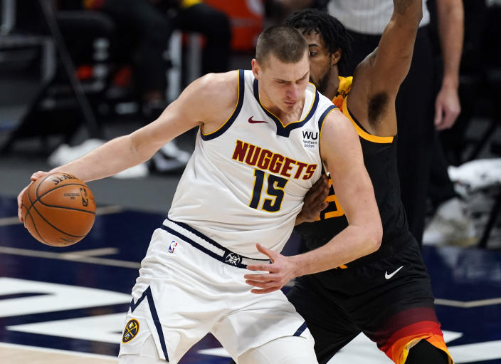 Denver Nuggets center Nikola Jokic, front, drives the lane as Utah Jazz center Derrick Favors defends in the first half of an NBA basketball game Sunday, Jan. 31, 2021, in Denver. (AP Photo/David Zalubowski)