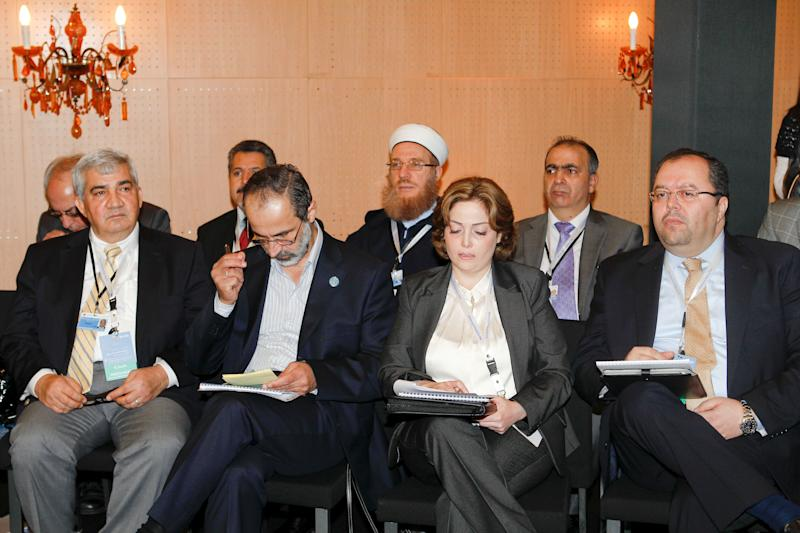 """Moaz al-Khatib, head of a new coalition of Syrian opposition groups, 2nd left, and Syrian delegation attend a meeting of the Friends of the Syrian People in Marrakech, Morocco, Wednesday Dec. 12, 2012. The Syrian opposition called for """"real support"""" and not just recognition on Wednesday, hours after the U.S. declared its new coalition was the """"legitimate representative"""" of its country's people. Bnner behind reads: 4th meeting of the group of """"Friends of the Syrian People"""". (AP Photo/Abdeljalil Bounhar)"""