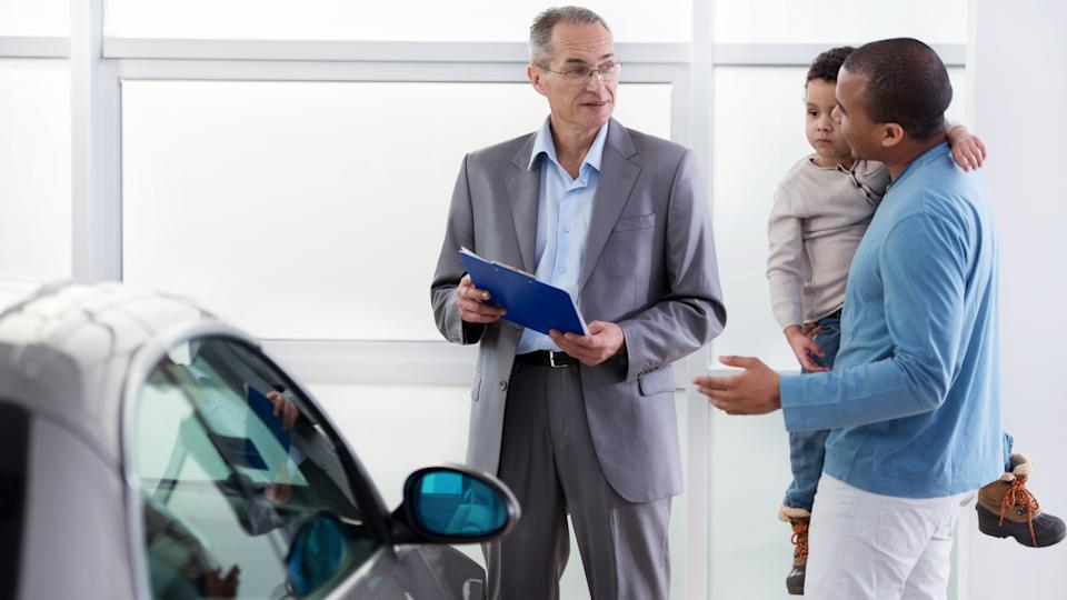 Smiling African American father holding his little boy and talking to the car salesperson and buying a new car.