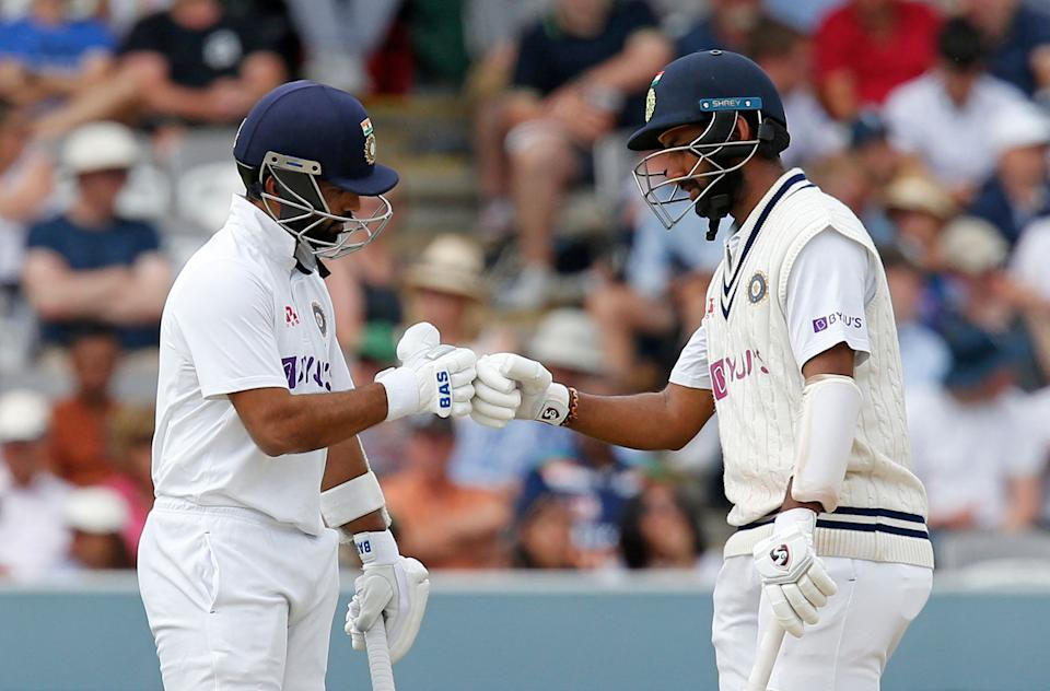 Pictured here, India's Ajinkya Rahane (L) and Cheteshwar Pujara tap gloves during the second Test match against England at Lord's.