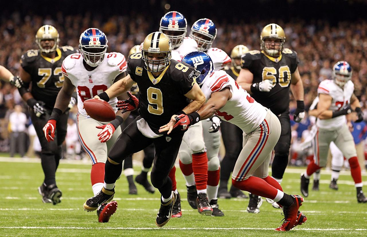 NEW ORLEANS, LA - NOVEMBER 28:  Drew Brees #9 of the New Orleans Saints runs for a touchdown against Deon Grant #34 of the New York Giants at Mercedes-Benz Superdome on November 28, 2011 in New Orleans, Louisiana.  (Photo by Ronald Martinez/Getty Images)
