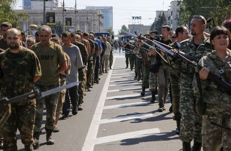 Armed pro-Russian separatists (R) escort a column of Ukrainian prisoners of war as they walk across the centre of Donetsk August 24, 2014. REUTERS/Maxim Shemetov