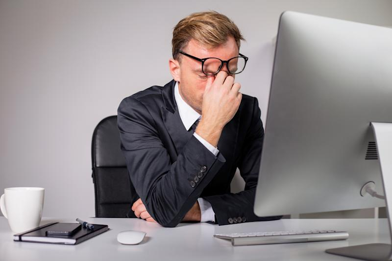 Frustrated businessman with glasses in front of a computer monitor.