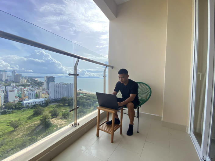 AP journalist Hau Dinh works on a laptop during a virus lockdown in Vung Tau, Vietnam on Sept. 13, 2021. Dinh set off from Hanoi for the seaside resort for a long weekend in mid-July. The trip came just as the delta variant began sweeping through Vietnam, sparking harsh lockdown measures that left him trapped away from home. Nine weeks later, he's still there. (AP Photo/Mathieu Le Besq)