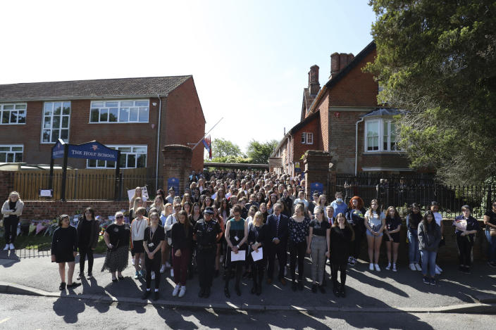 Colleagues and pupils of teacher James Furlong stand together to take part in a minute of silence at The Holt School. (PA)