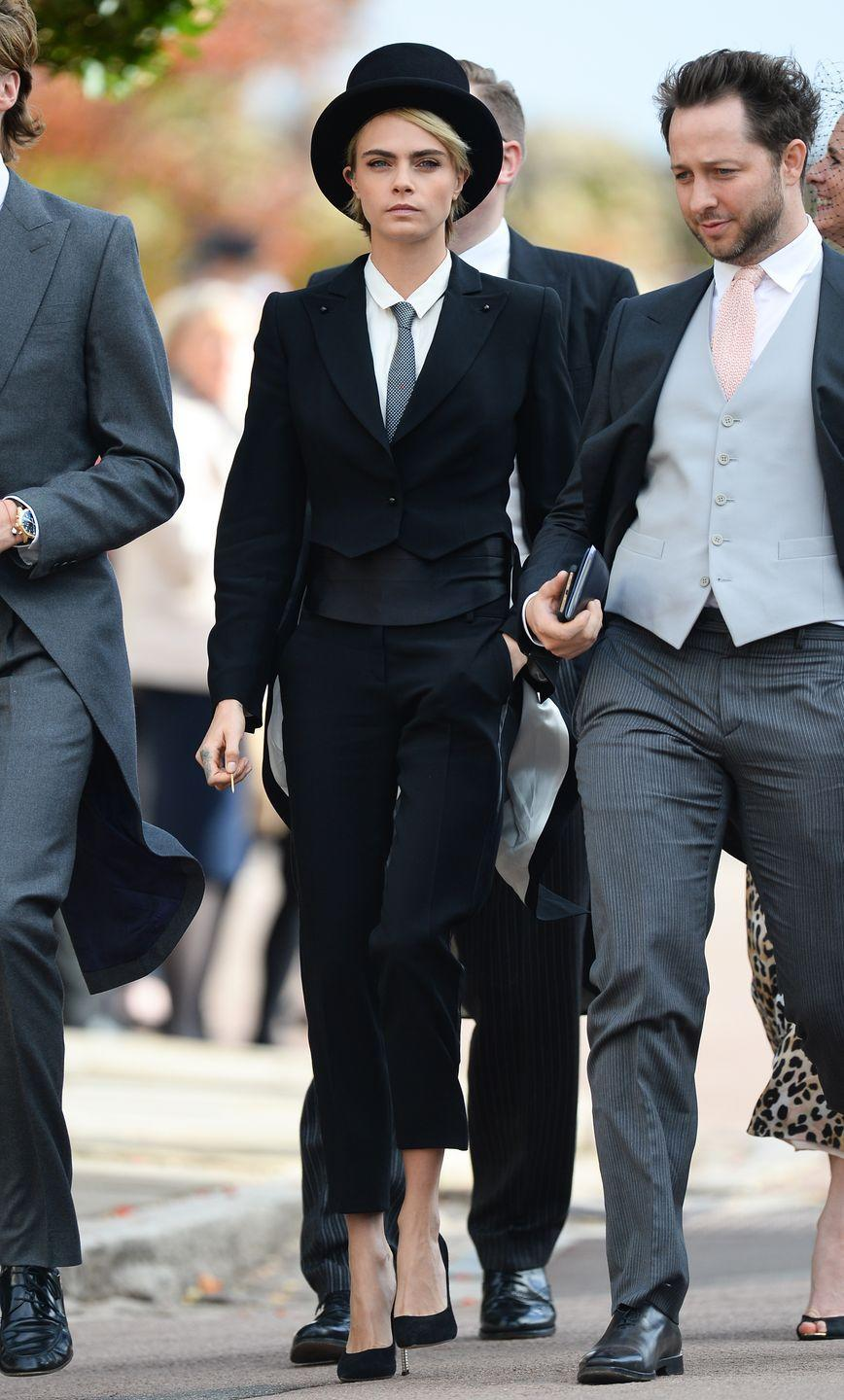 <p>Cara Delevingne took a unique approach by wearing a top hat to accessorize her tailored suit. </p>