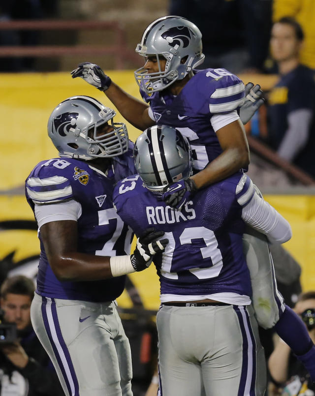 Kansas State wide receiver Tyler Lockett (16) celebrate his touchdown with teammates Tavon Rooks (73) and Cornelius Lucas (78) during the first half of the Buffalo Wild Wings Bowl NCAA college football game against Michigan, Saturday, Dec. 28, 2013, in Tempe, Ariz. (AP Photo/Matt York)
