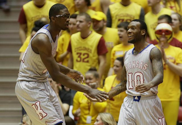 Kansas guard Naadir Tharpe, right, celebrates with teammate Joel Embiid after making a basket during the first half of an NCAA college basketball game against Iowa State, Monday, Jan. 13, 2014, in Ames, Iowa. (AP Photo/Charlie Neibergall)