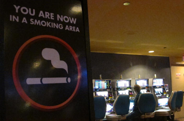 This March 9, 2016 photo shows a sign denoting a smoking section of the casino floor at the Tropicana casino in Atlantic City, N.J. On Thursday, April 15, 2021, health advocates, smoking opponents and some New Jersey lawmakers called for the state's temporary ban on casino smoking, imposed last year due to the coronavirus pandemic, be made permanent once the outbreak ends. (AP Photo/Wayne Parry)